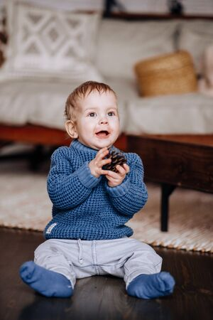 A blond boy in a blue sweater crawls on the wooden floor. A one-year-old child plays with a bump.