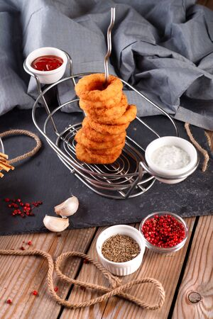 Fried breaded onion rings with beer sauce on a wooden table background