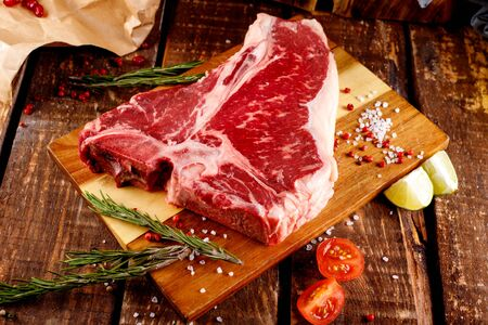 Raw T-bone Steak for grill or BBQ on cutting board over aged wooden background, top view