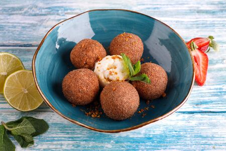Tiramisu flavored chocolate truffle pralines sweet mini snack balls on a blue plate background