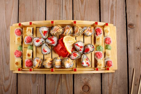 large colorful set of sushi in a square plate. on a wooden background Banco de Imagens