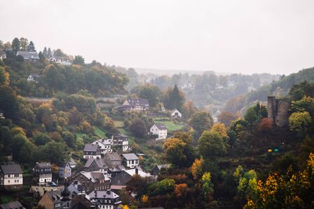 cloudy autumn panorama of the old city. Monschau, Germany. Green hills and gray mica roofs.