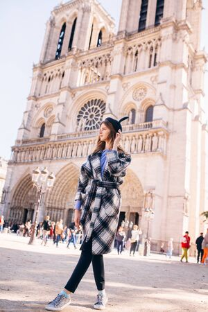 beautiful girl in a mikimaus hat in a beautiful coat on the background of the Parisian Cathedral of Notre Dame