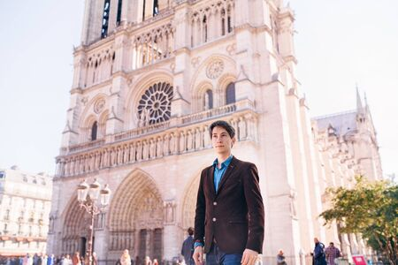 a young man poses against the backdrop of Notre Dame Cathedral in Paris.France