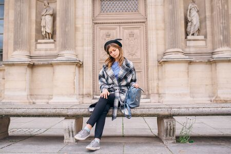 A girl in a beautiful coat is sitting on a bench. Concept of visiting France and historical buildings.