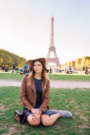 Beautiful girl sitting in Paris against the backdrop of the Eiffel tower