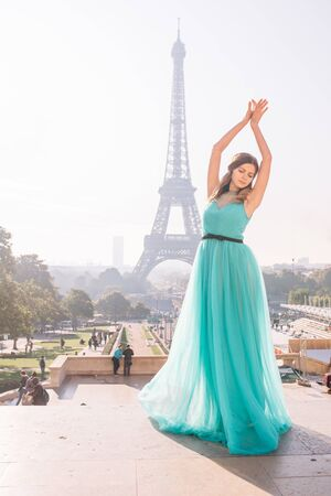 a girl in Paris in a green dress against the backdrop of the Eiffel tower elegant on the Trocadero square in summer a luxurious beautiful figure of a French woman.