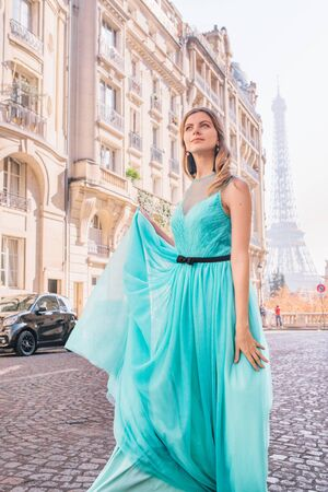 Beautiful young girl in a dress on the street with a view of the Eiffel tower, in Paris Banque d'images