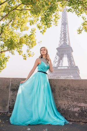 A young beautiful and elegant girl in a blue and green dress stands against the background of the Eiffel tower in Paris.France