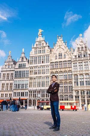 a man on Antwerp square with the city hall and Brabo monument in the Old city, Belgium