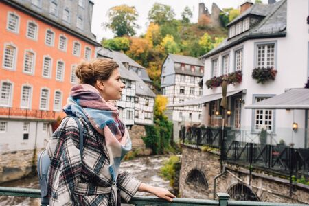 a girl in a coat walks in Monschau, Germany, despite the wet weather