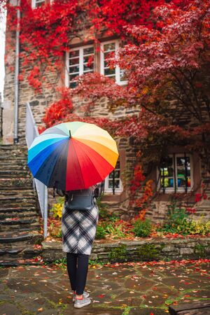 a girl in a coat walks in Monschau with a bright umbrella, despite the wet weather