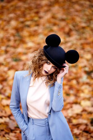 Cute girl on the street in a funny hat. Autumn leave. The Ears Of Mickey Mouse.