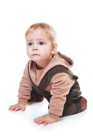 fashionable portrait of a charming one-year-old little boy on a white background, dressed in brown trousers, a beige hoodie, Banque d'images