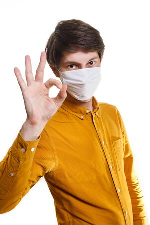 Stop the infection A healthy man shows the OK gesture. In the photo, the man is wearing a protective mask against infectious diseases and flu. The concept of health care.