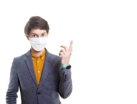 A recovered man in a medical mask, shirt, gestures at an empty background