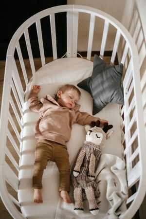 Cute little 1-year-old baby is lying on a cot while sleeping with Windows of light on his face, daytime sleep concept