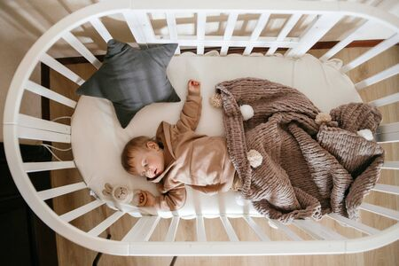 Cute little 1-year-old baby is lying on a cot while sleeping with Windows of light on his face, daytime sleep concept Standard-Bild