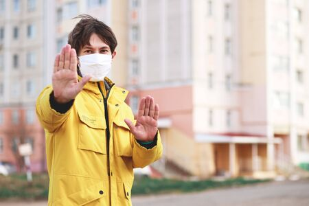 A handsome young man standing outdoors in a medical mask shows a stop gesture