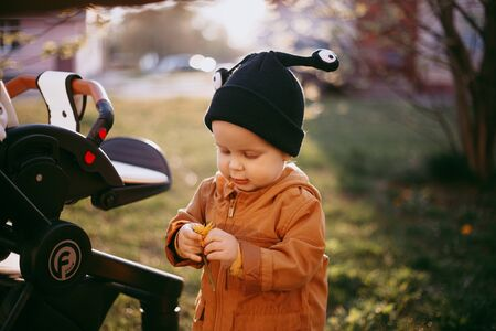 portrait of a one year old boy with a snail wool cap on the background of nature
