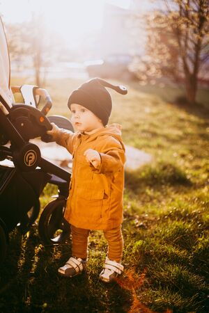portrait of a one year old boy with a snail wool cap on the background of nature Stock Photo