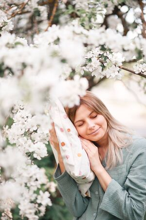 a girl hugs a large pillow with a casual expression on her face on a day off wears sleeping blue pajamas in a blooming Apple orchard in spring.