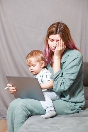 A young woman works at home with a tablet computer, along with a child.the son wants to communicate with his mother, they make noise and interfere with work.Self-isolation during the coronovirus pandemic