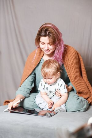 A young woman works at home with a tablet computer, along with a child.the son wants to communicate with his mother, they make noise and interfere with work.Self-isolation during the coronovirus pandemic Stock Photo