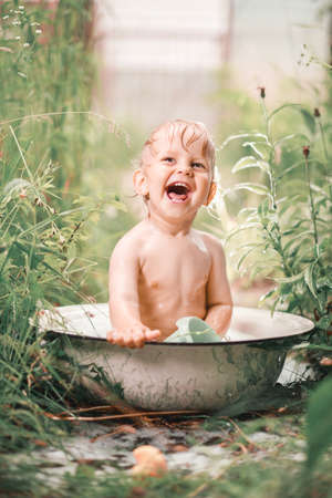 Sunny summer day.A charming little boy is bathing in a baby bath on a green lawn.He splashed and laughed.