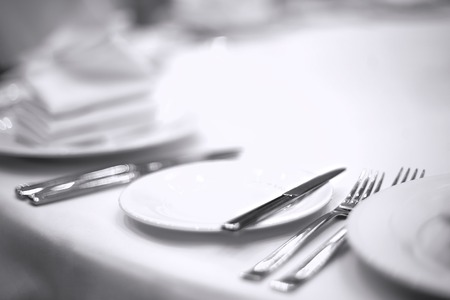 plates napkins forks knives on a white tablecloth Foto de archivo