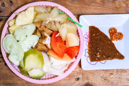 Indonesian traditional snack, (Rujak manis : Indonesian spelling), consists of slices of pineapple, raw mango, jicama, cucumber, Ambarella, star fruit, papaya and fried tofu.