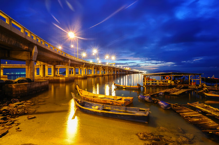 Fisherman boats at blue hour on the beach nearest Penang Bridge Malaysia Flare lens
