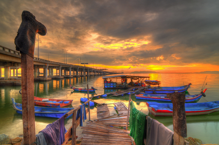 penang: Fisherman boats at sunrise time on the beach. The bridge is the Penang Bridge in Malaysia. HDR Image