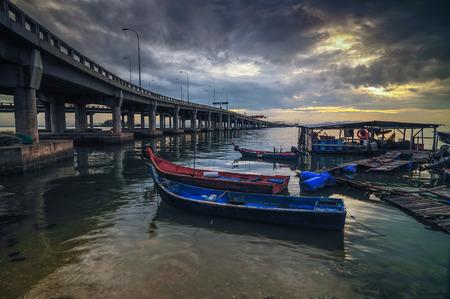 ビーチで日の出時漁師船。橋は、マレーシアのペナン ブリッジです。 写真素材