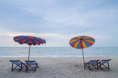 sun umbrella: Four lounge chairs with sun umbrella on a beach