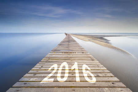 proceeding: Long jetty leading over the ocean to the horizon at dawn. On the jetty is written the word 2016. Concept for proceeding to success in new year Stock Photo