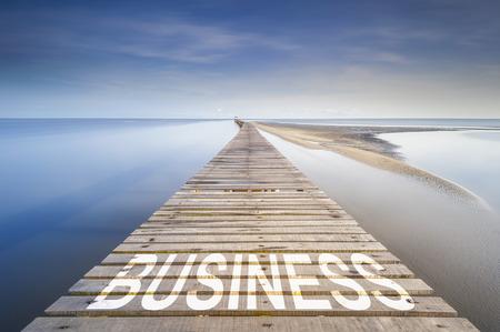 青い空、地平線に海の上で無限の桟橋。桟橋でビジネス単語を書かれています。ビジネスの成功に進むのためのコンセプトです。