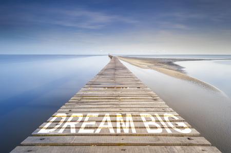 青い空、地平線に海の上で無限の桟橋。桟橋に大きな夢の言葉を書かれています。成功に進むのためのコンセプトです。