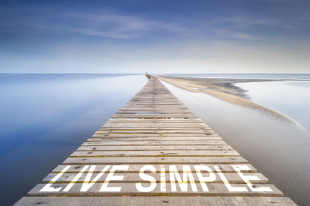 find similar images: Preview Save to a lightbox  Find Similar Images  Share Stock Photo: Long jetty at ocean to the horizon. On the jetty is written the Live Simple. Concept for proceeding to success.