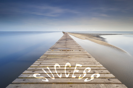 proceeding: Endless jetty at morning over a ocean to the horizon. On the jetty is written the word success. Concept for proceeding to success. Stock Photo