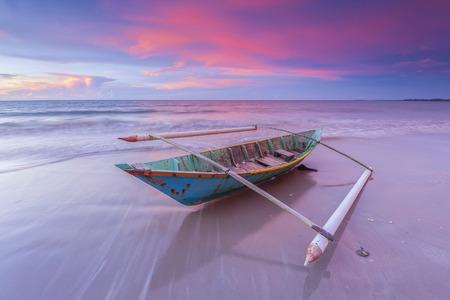 美しい夕日と放棄された漁船 写真素材