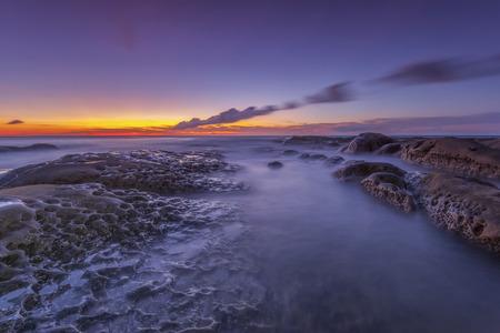 フォア グラウンドで岩と夜明けオーストラリア シースケープ