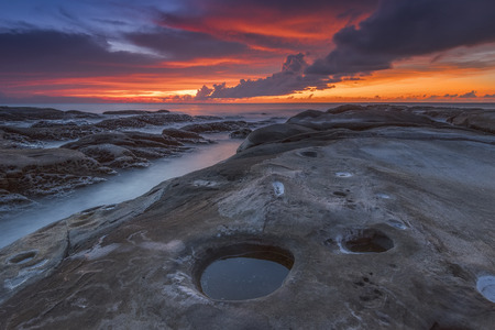 Australian seascape at dawn with rocks in foreground