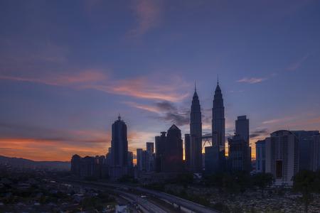 kampung: KUALA LUMPUR, MALAYSIA - DEC 12, 2015; The silhouette of Petronas Towers from the KL City Park during sunrise at Kampung Baru, Malaysia