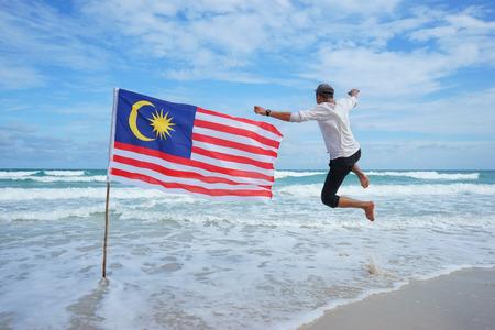 独立記念日ムルデカ日コンセプト - 空気中のジャンプ正体不明の男性がマレーシアのフラグを保持しています。