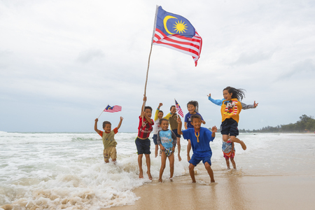 KUDAT SABAH, MALAYSIA - 6th AUGUST 2016 ; Independence Day / Merdeka day concept - Local kids holding a Malaysian flag and jumping on beach 報道画像