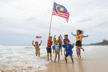 クダット マレーシア ・ サバ州 2016 年 8 月 6 日;独立記念日・ ムルデカ日コンセプト - ローカル子供のマレーシアのフラグを保持していると、ビーチにジャンプ 写真素材 - 65469622