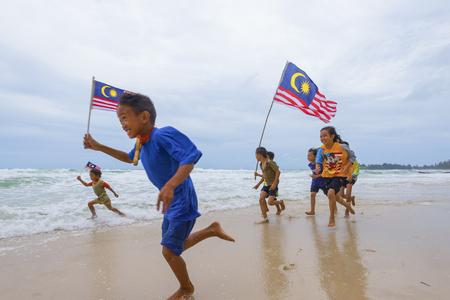 マレーシア ・ サバ州: 2016 年 8 月 6 日: マレーシアの国旗を振っていると実行しているマレーシアの子ども達。独立記念日のお祝い 報道画像