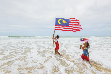 マレーシア ・ サバ州: 2016 年 8 月 6 日: マレーシアの国旗を振っていると実行しているマレーシアの子ども達。独立記念日のお祝い 写真素材 - 65469626