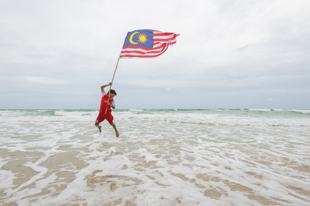 KUDAT SABAH, MALAYSIA - 6th AUGUST 2016 ; Independence Day / Merdeka day concept - The local boy jumping in the air holding a Malaysian flag 報道画像